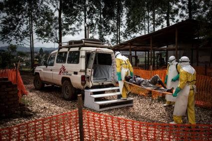 Des professionnels de santé acheminent vers l'hôpital un malade diagnostiqué positif dans un centre de traitement Ebola de Médecins Sans Frontières (MSF) à Butembo, dans la province du Nord-Kivu, en RDC. ©John Wessels for MSF