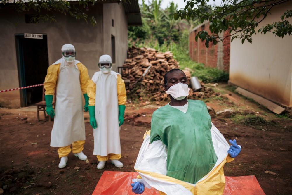Des volontaires de la Croix-Rouge congolaise ôtent minutieusement leurs vêtements et accessoires de protection, selon une procédure très précise, dans un centre de santé du Nord-Kivu, à Kalunguta, en RDC. Une étape cruciale et potentiellement dangereuse. ©Alexis Huguet pour MSF